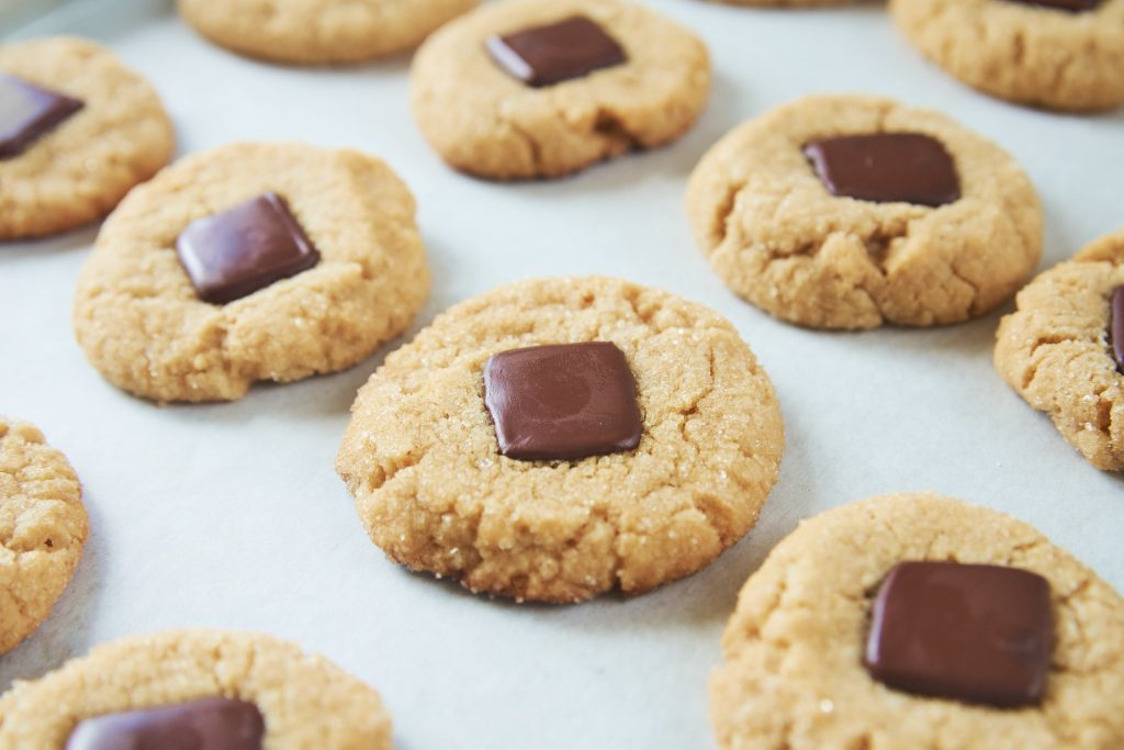 vegan peanut butter blossoms cooling on cookie sheet with parchment paper