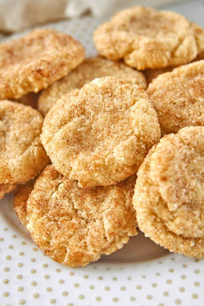 close up of vegan snickerdoodles on a plate with cinnamon sugar dusting