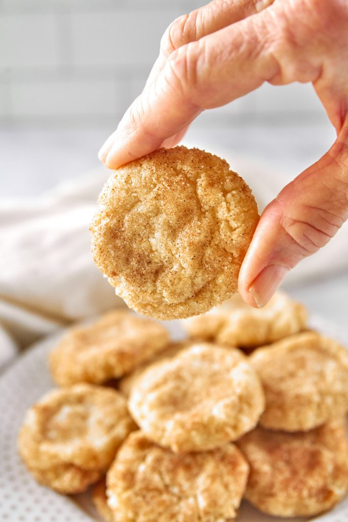 hand picking up a vegan snickerdoodle cookie off a plate