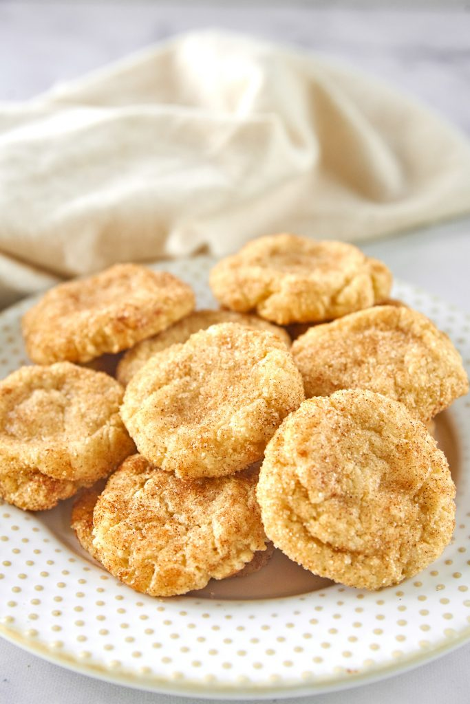 easy vegan snickerdoodles on a plate with a dish towel