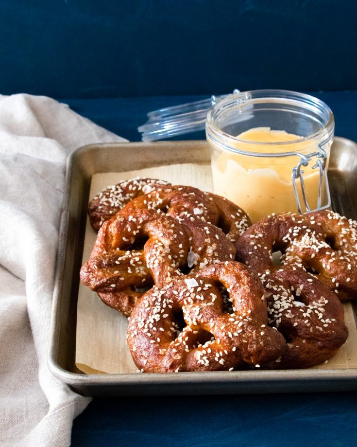 vegan soft pretzels with vegan beer cheese on baking tray