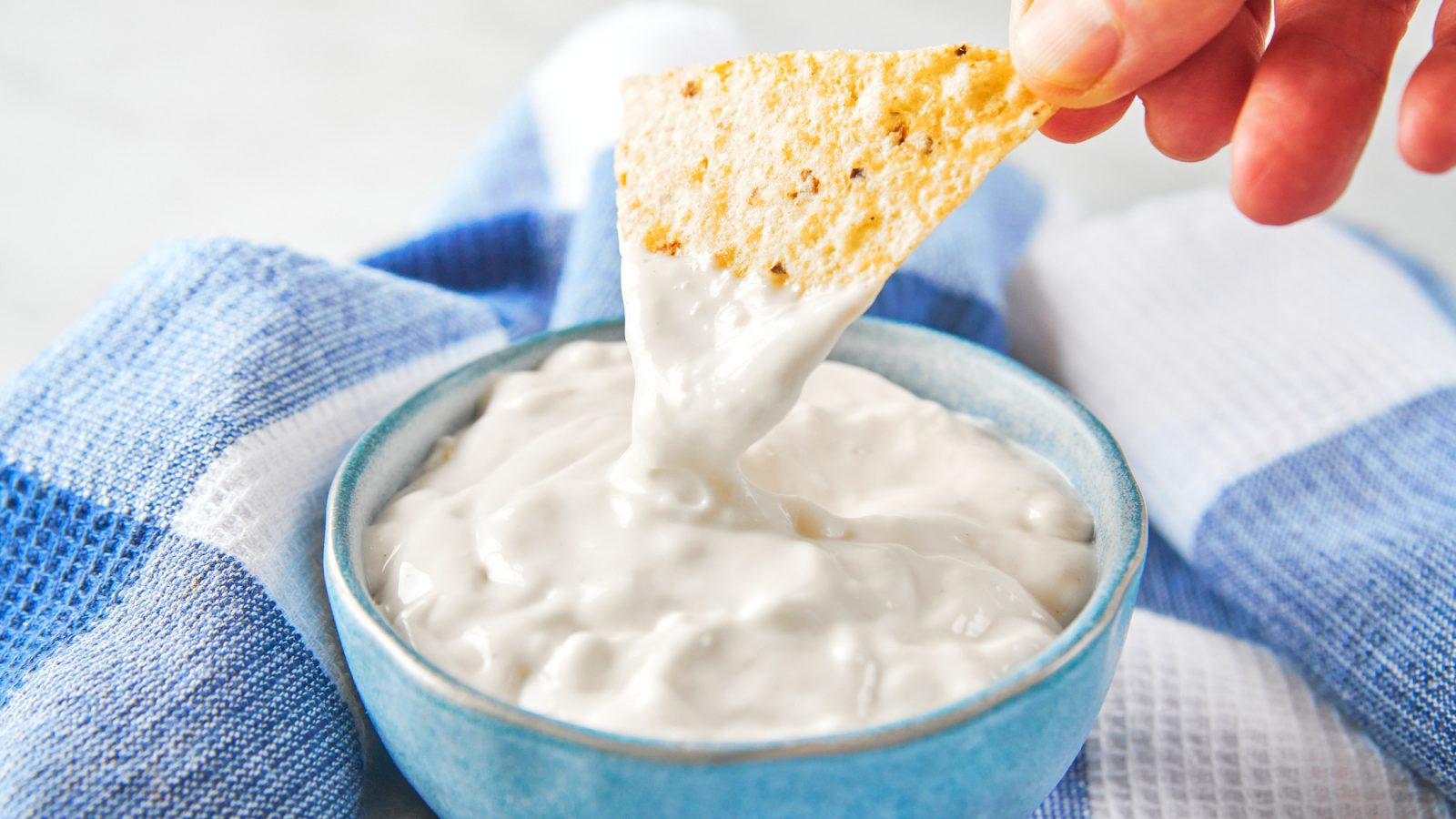 chip scooping out vegan sour cream from a bowl