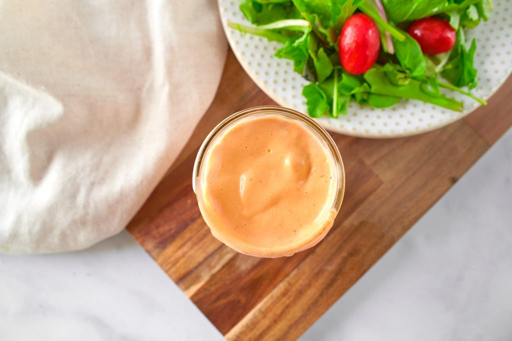 above view of vegan thousand island dressing in a jar with a salad on the side