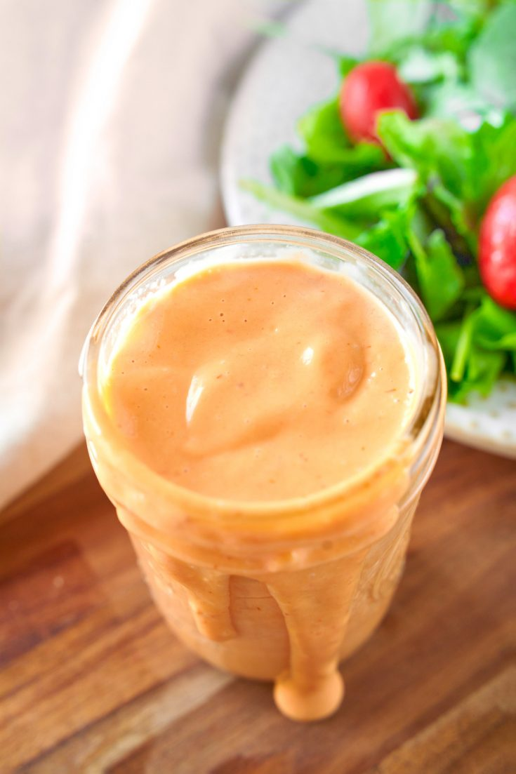 vegan thousand island dressing in jar with salad in the background