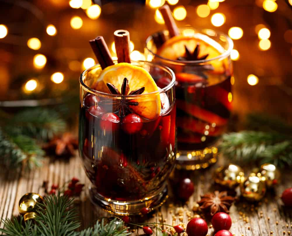 Photo of mulled wine in two glasses with cranberries, oranges, and cinnamon sticks.