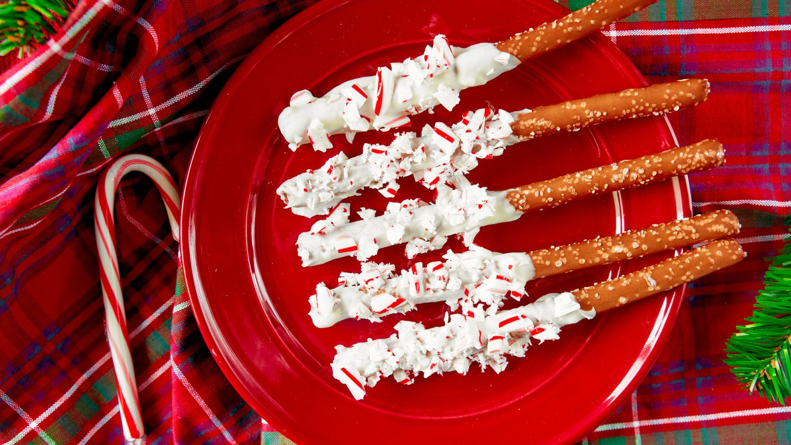 christmas pretzel rods dipped in white chocolate and topped with peppermint