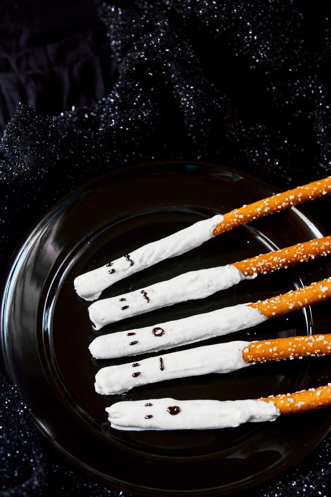 ghost halloween pretzel rods on a black plate