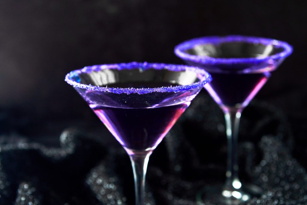 two purple Halloween cocktails with purple rims