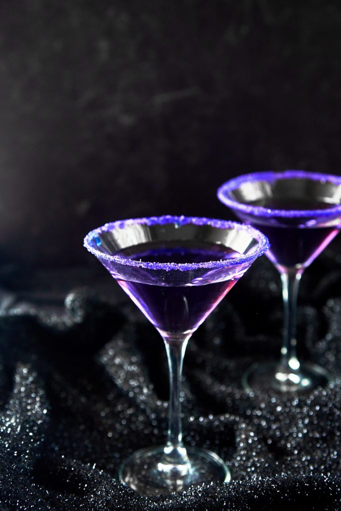 two purple halloween cocktails on a black background
