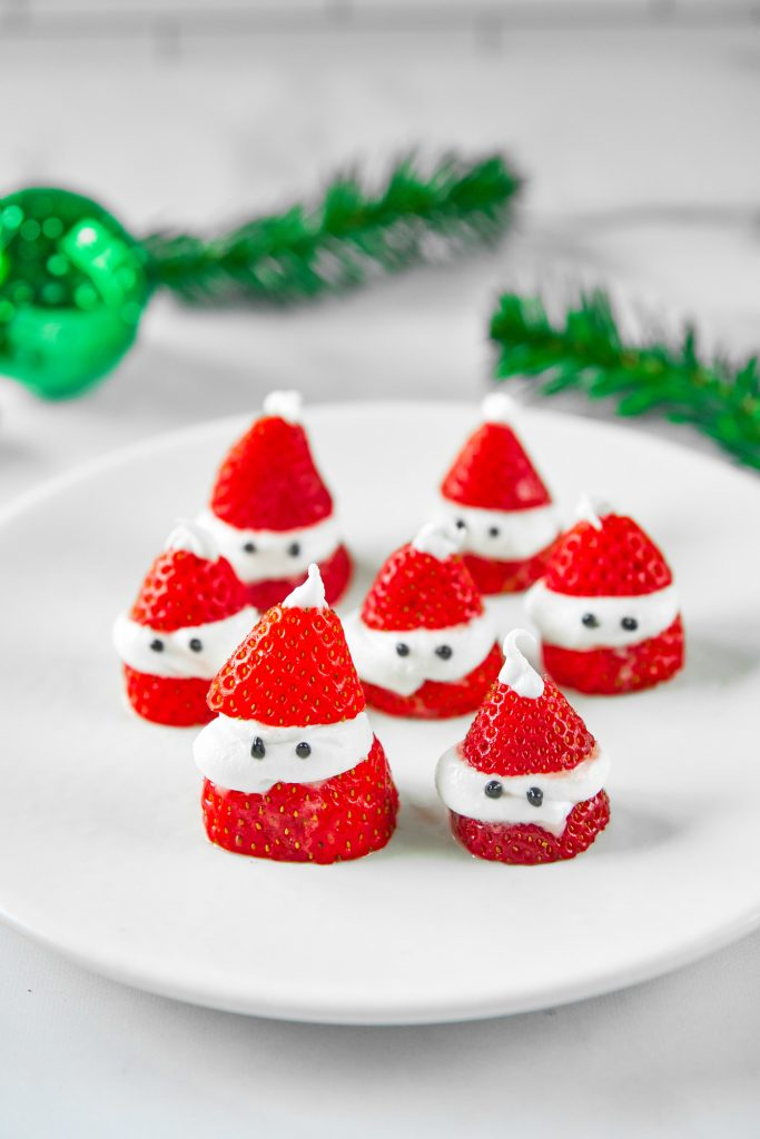 stuffed Santa strawberries on plate with greenery in the background