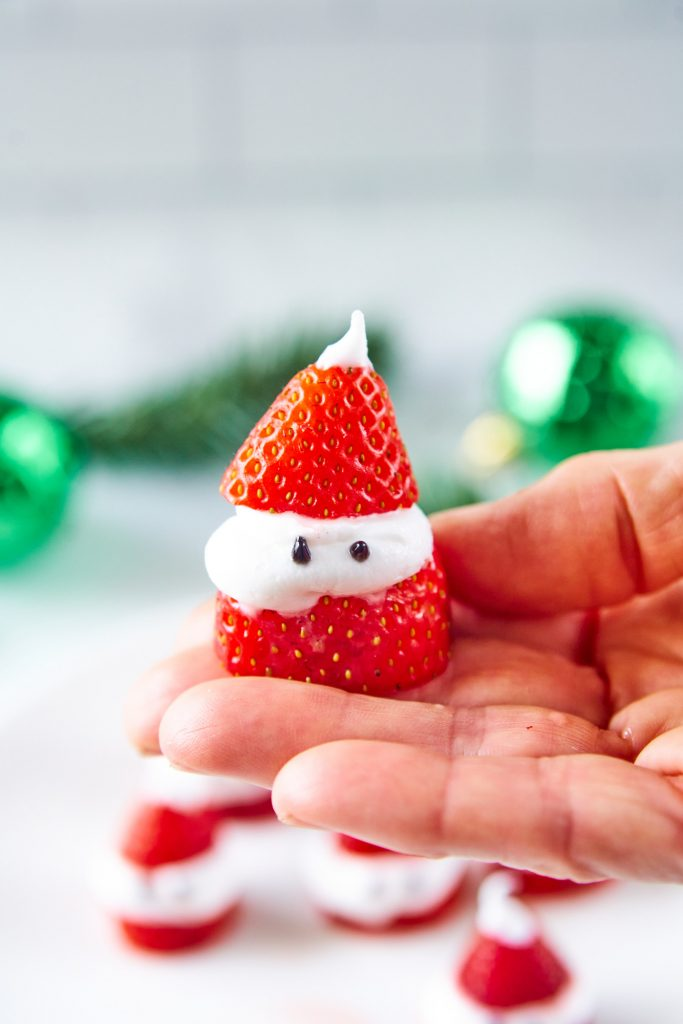 hand holding a strawberry Santa Claus
