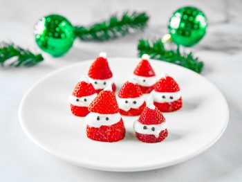 santa strawberries on plate with green ornaments in the background