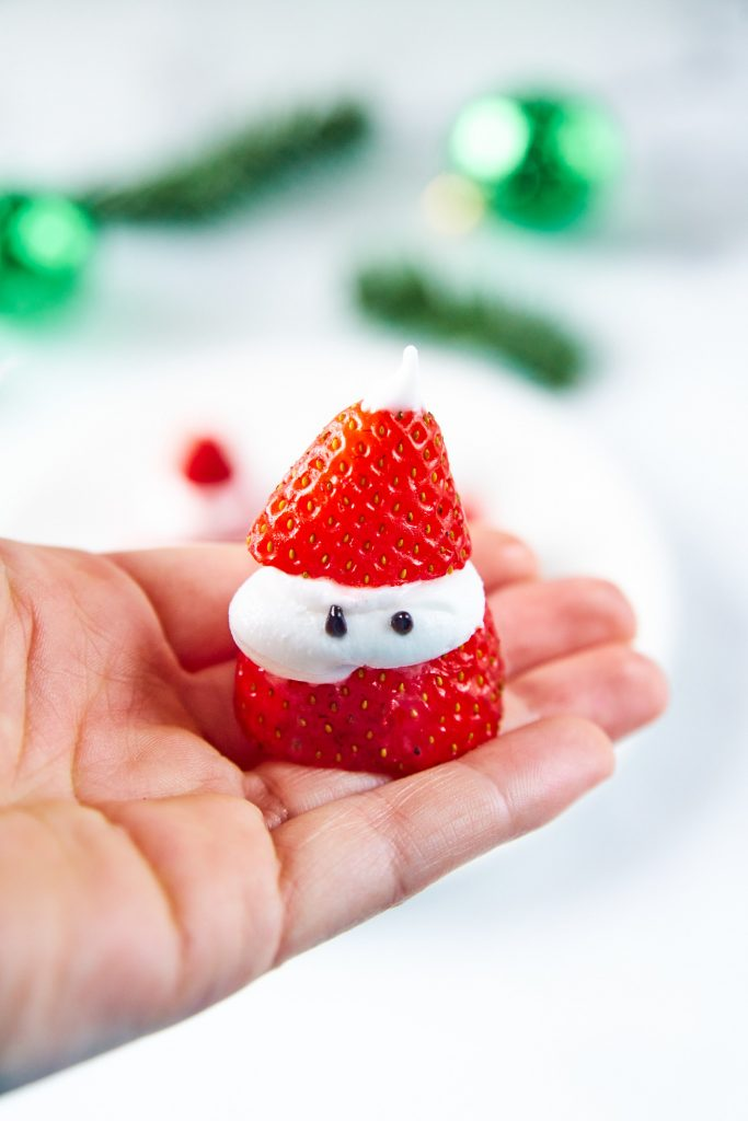 hand holding a strawberry that looks like Santa Claus