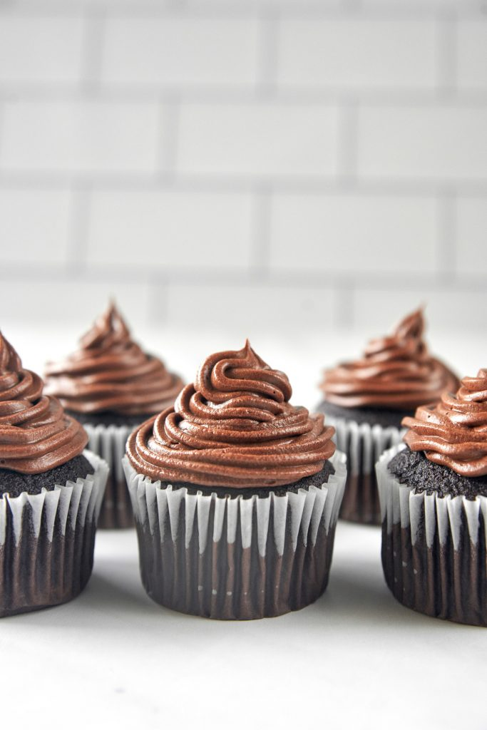 lots of vegan chocolate cupcakes with chocolate icing