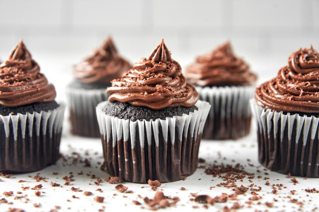 vegan chocolate cupcakes with chocolate icing and shavings