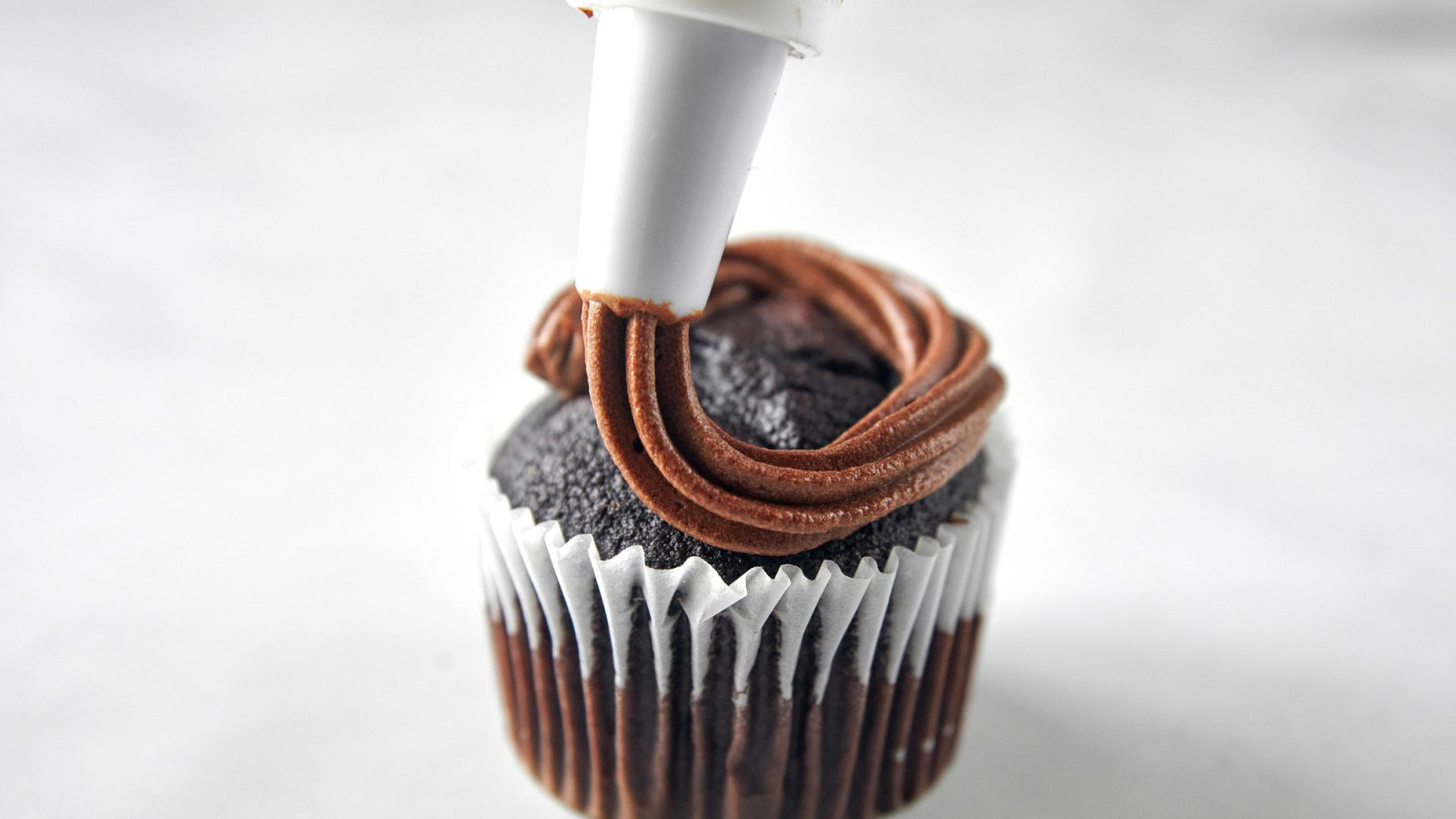 vegan chocolate frosting being piped onto a cupcake
