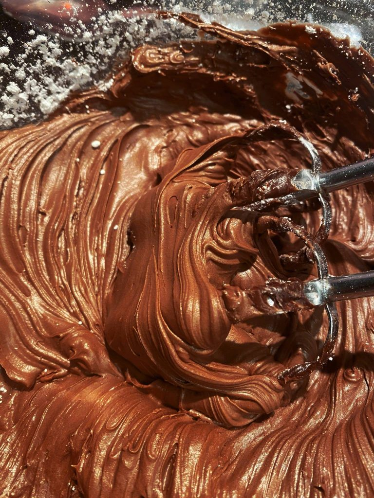 vegan chocolate frosting being made in a bowl