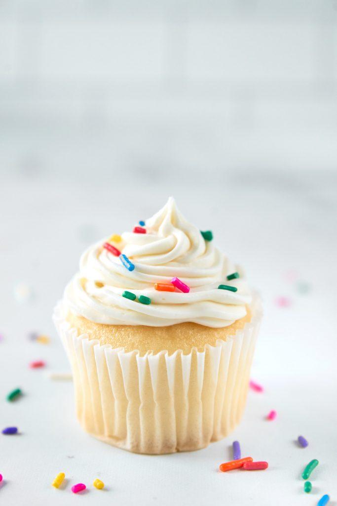 single vegan vanilla cupcake with sprinkles