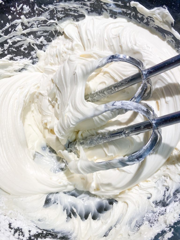beating vegan vanilla frosting in bowl