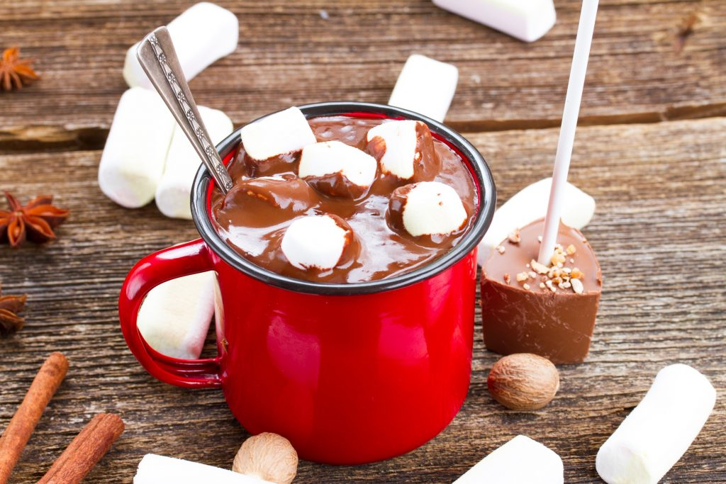hot chocolate on a stick being used to make hot chocolate in a red cup