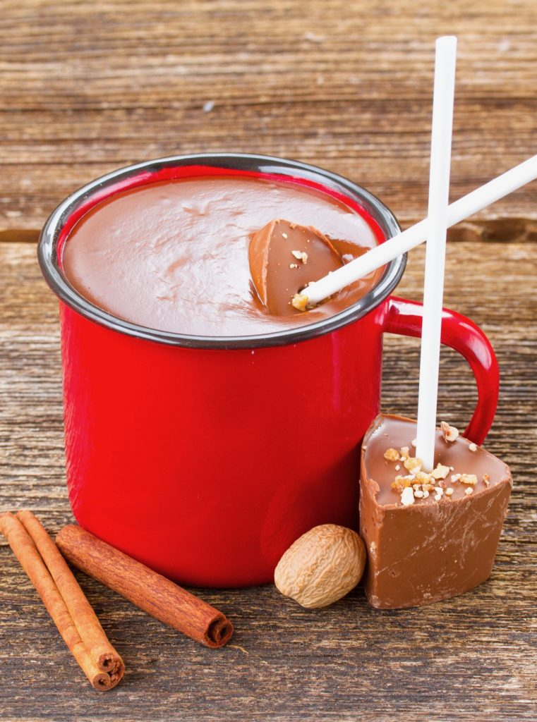 hot chocolate sticks being used to make hot chocolate in a red mug
