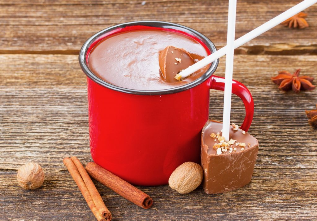 hot chocolate sticks lying next to a cup of hot chocolate in a red mug