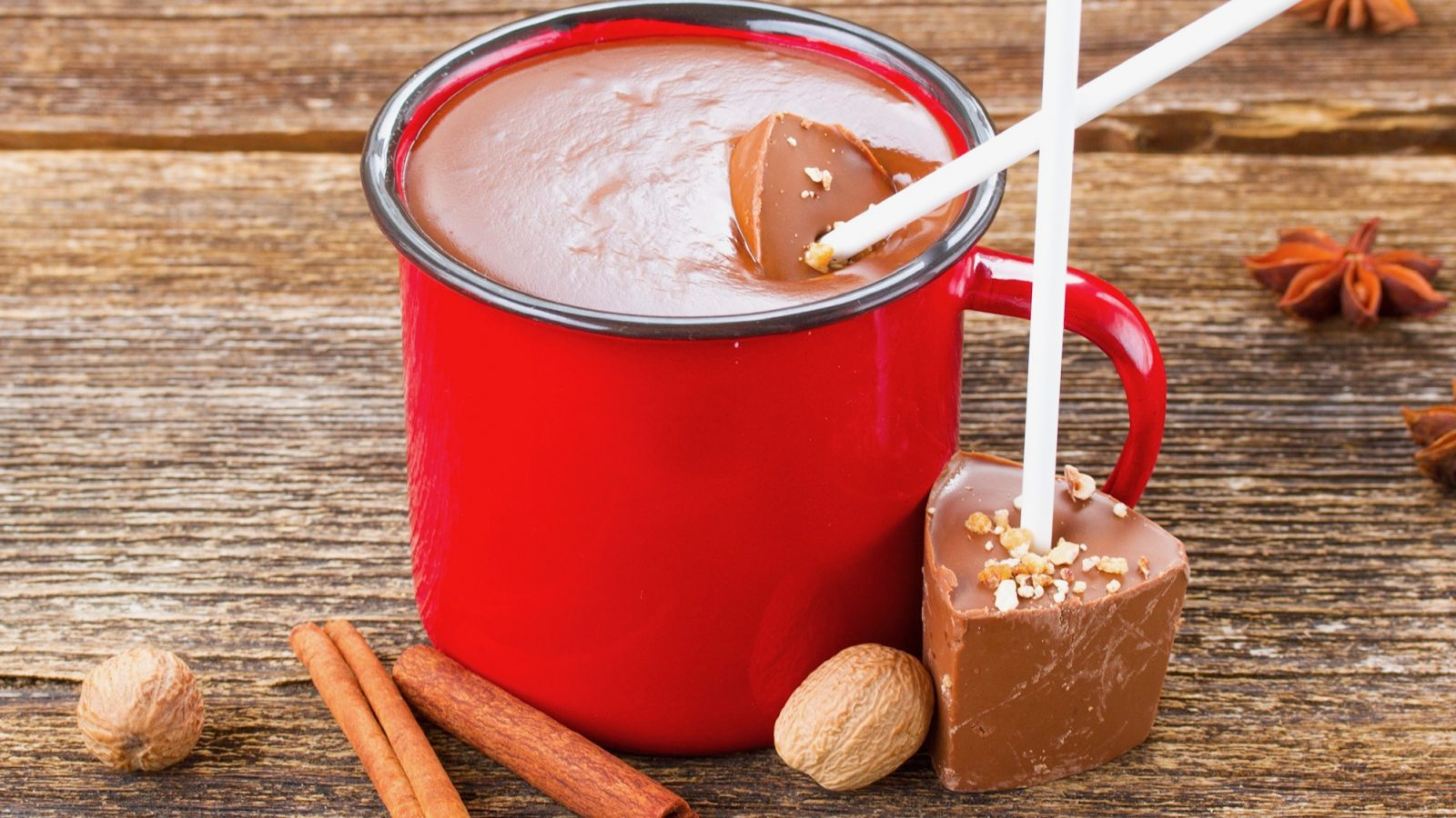 hot chocolate sticks that are vegan being dipped into a red mug