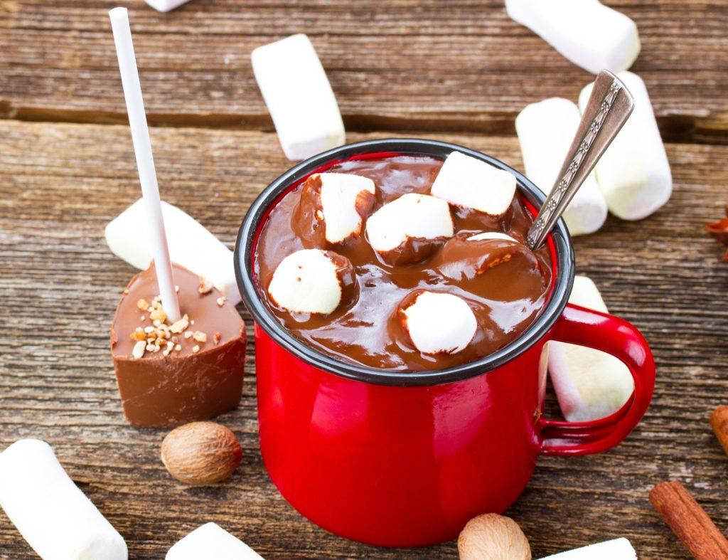 vegan hot chocolate on a stick near a red mug