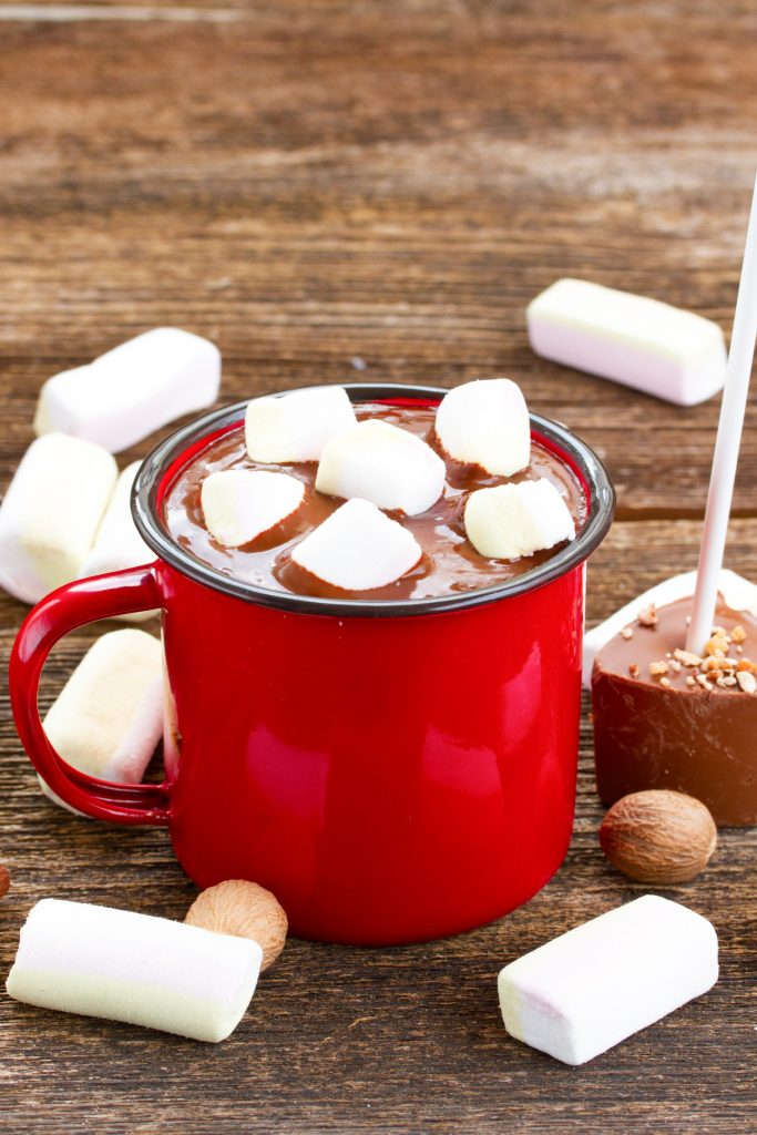 hot chocolate sticks with a red cup of liquid and marshmallows