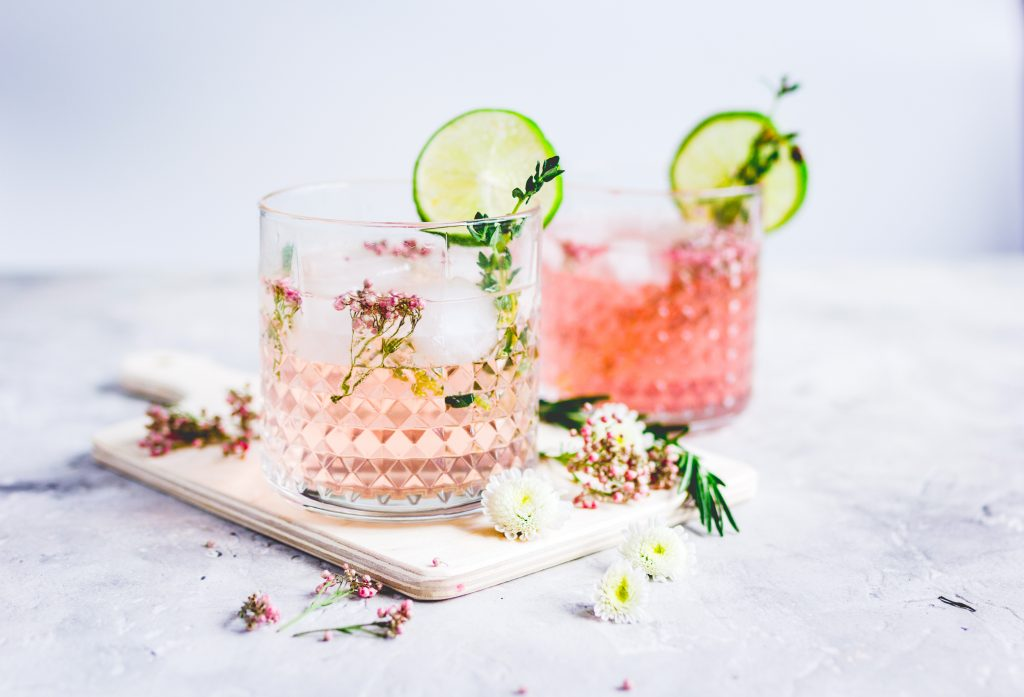two cups of pink vodka lemonade with flowers for garnish