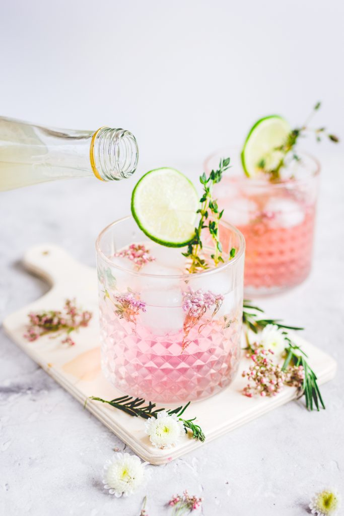 pouring liquid into pink vodka lemonade garnished with flowers