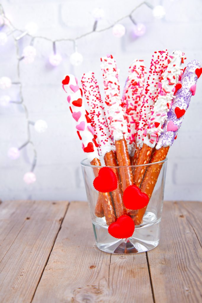 valentines day pretzel rods in a jar on a brown background