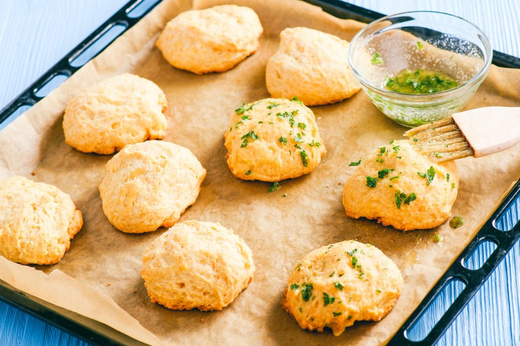 brushing vegan cheddar biscuits with oil and parsley