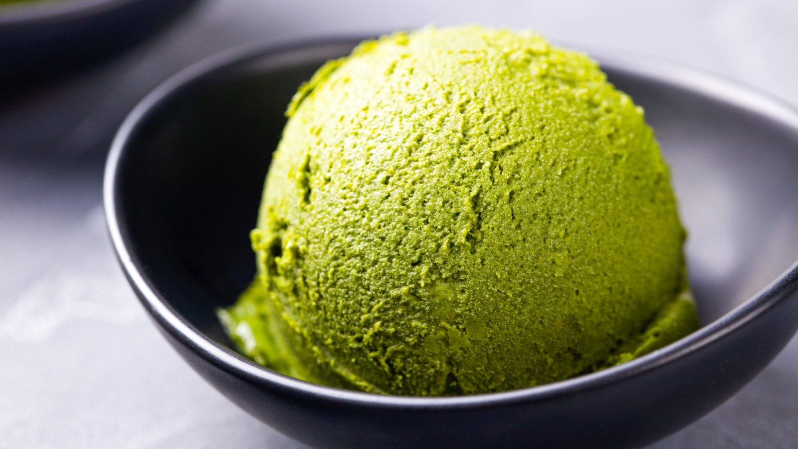 scoop of vegan matcha ice cream in a black bowl