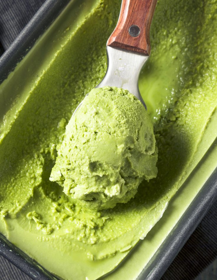vegan matcha ice cream in a container with a scoop