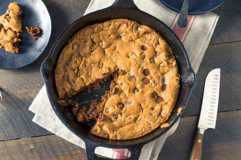 vegan skillet cookie with a slice taken out of it as seen from above on a table