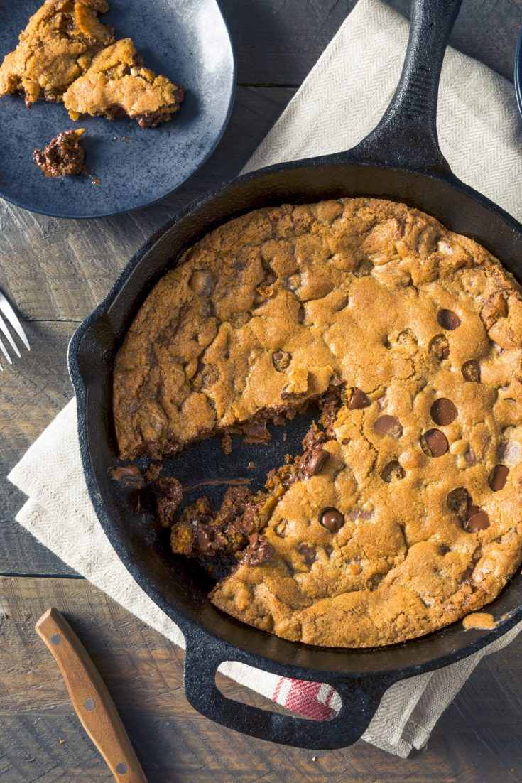 vegan skillet cookie with a slice being taken out of it