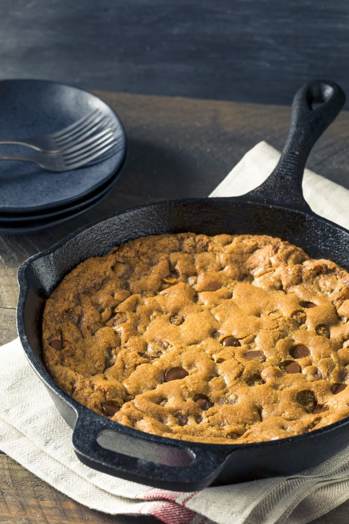 vegan skillet cookie not cut being baked in a cast iron pan
