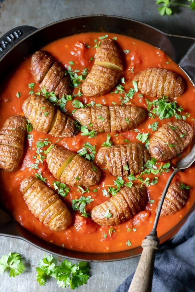 Photo of Baby Hasselback Potatoes being served in a cast iron pan with harissa-spiced tomatoes.