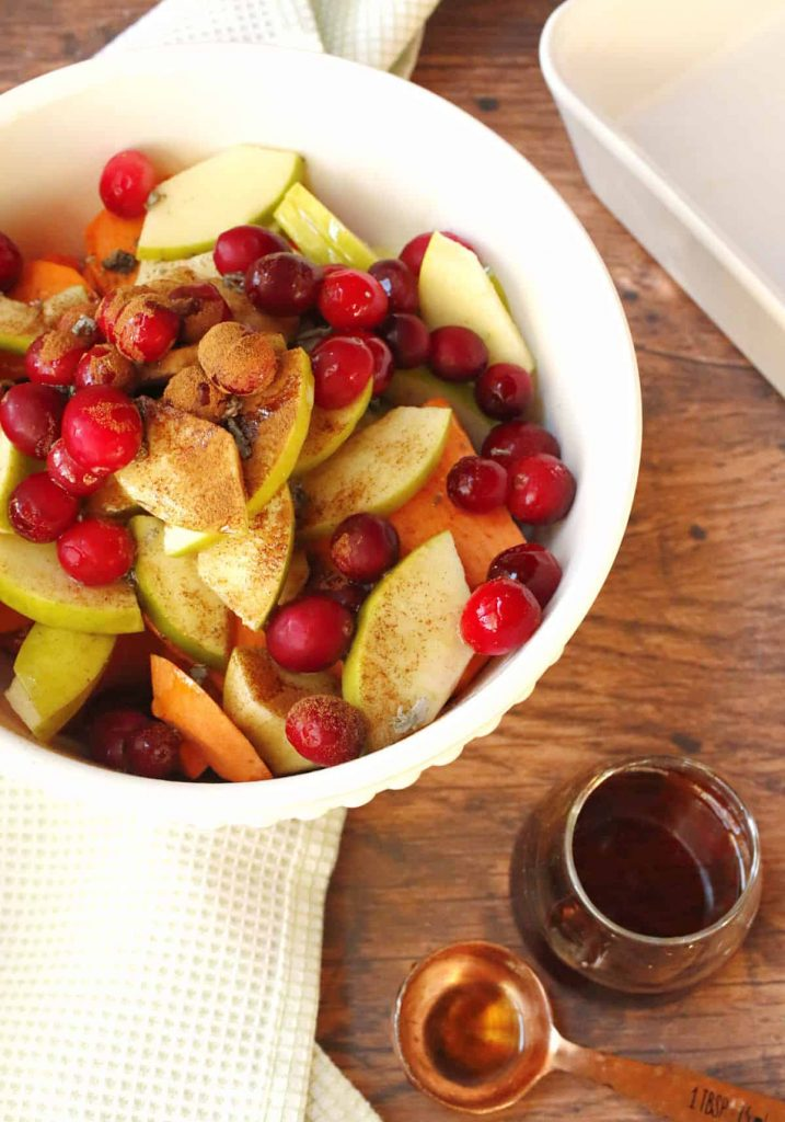 Photo of potatoes, apples, and cranberries in a bowl being prepared for a casserole.