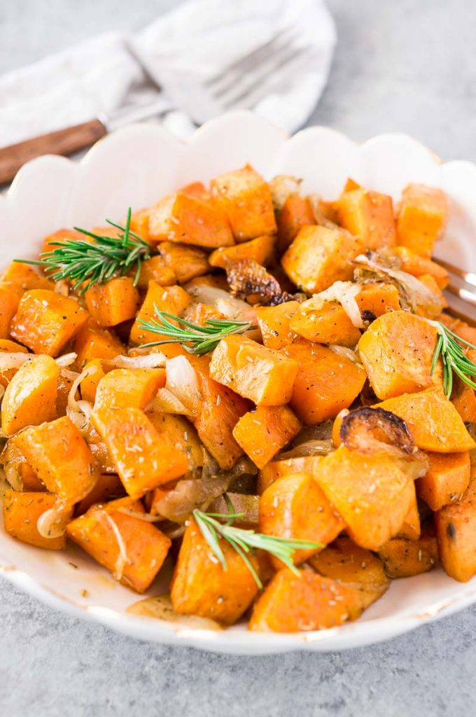 Photo of Roasted Sweet Potatoes and Onions being served in a scalloped white dish.