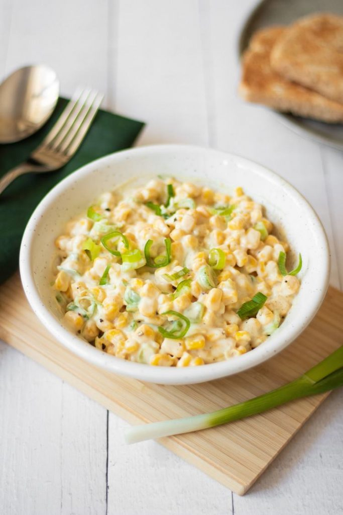 Photo of a small white bowl serving Creamy Vegan Corn Salad.