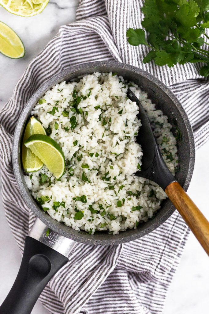 Photo of cilantro lime rice being served from a pot with a wooden spoon.