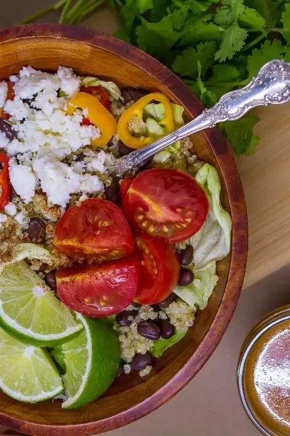 Photo of Southwest Salad With Quinoa & Black Beans being served in a wooden bowl.