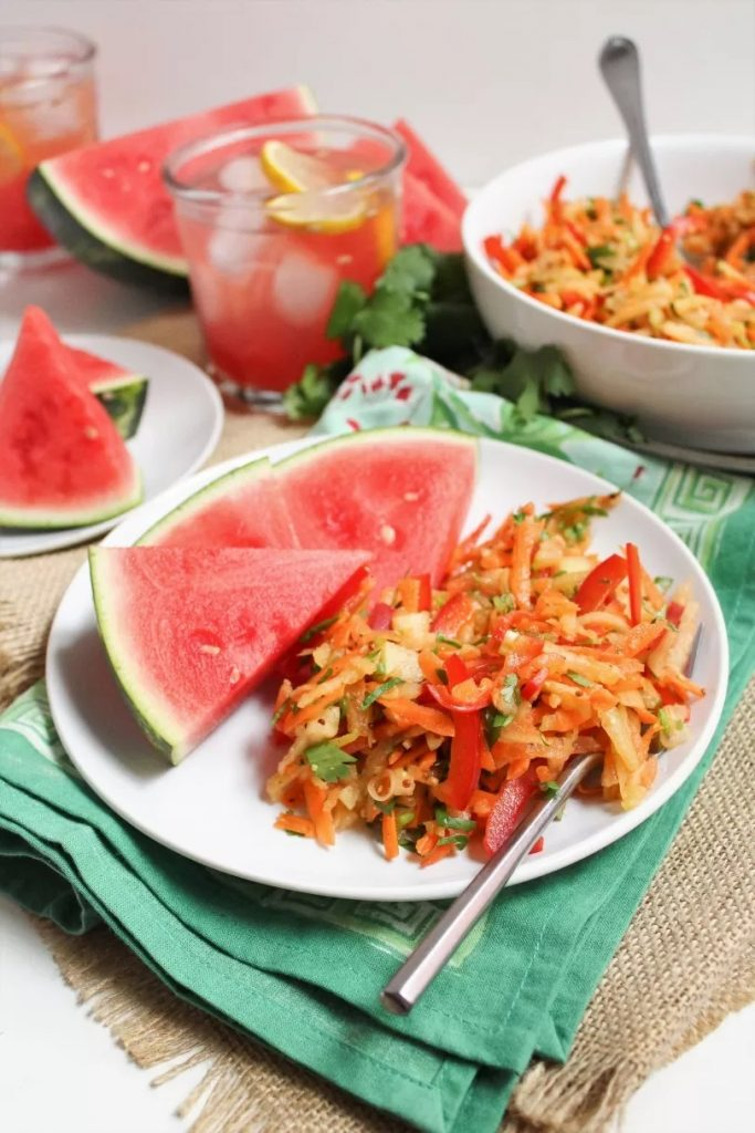 Photo of watermelon rind coleslaw being served with sliced watermelon.