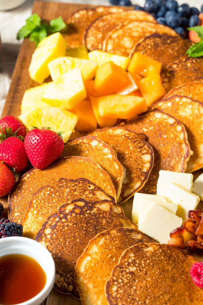 close up of pancakes on a breakfast board with fruit