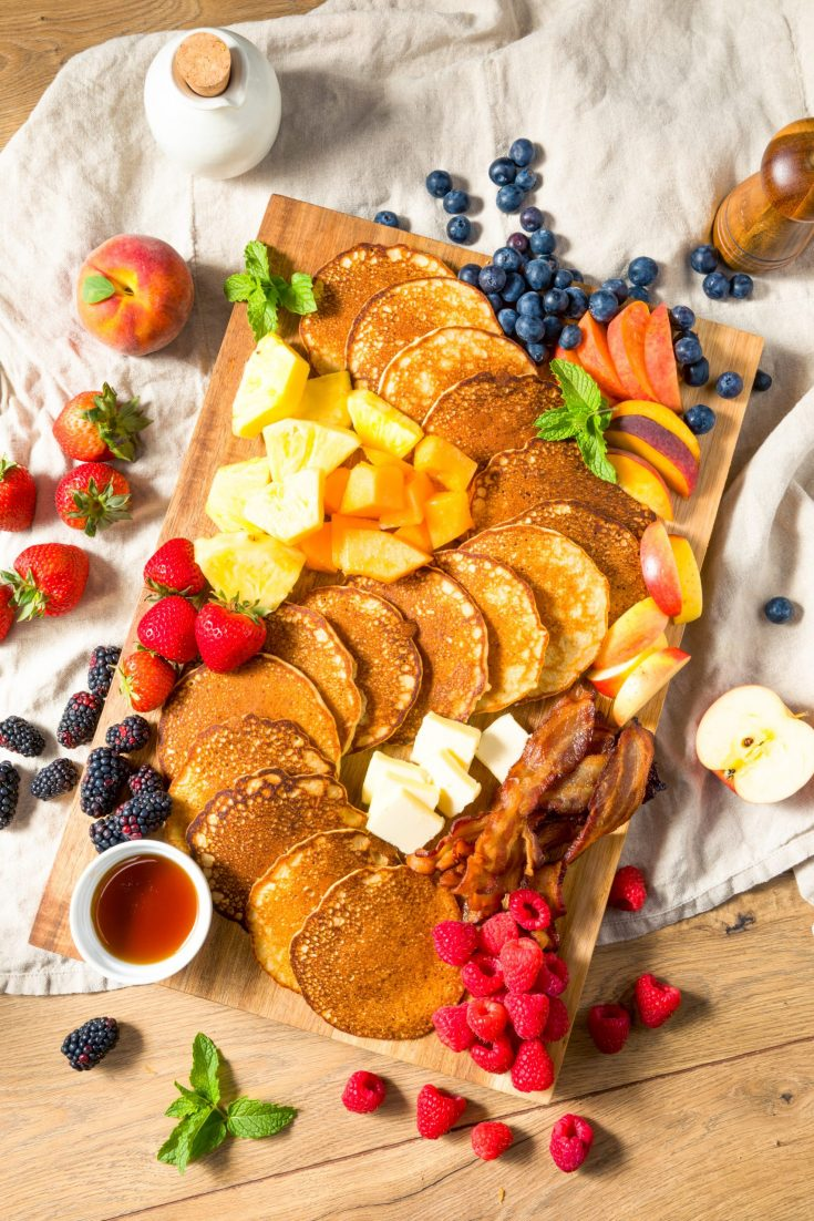 breakfast charcuterie board with pancakes, fruit, vegan bacon and more