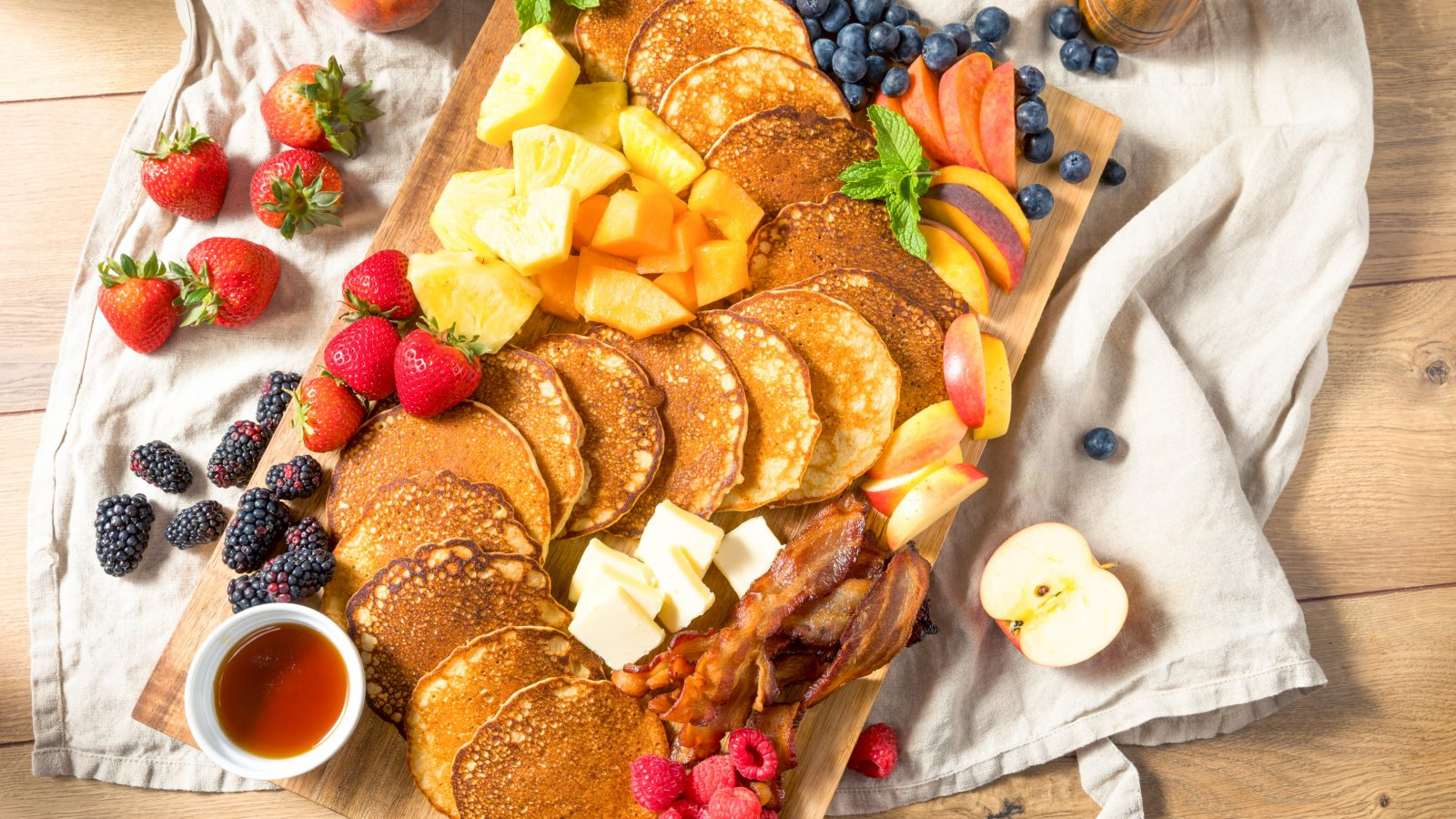 breakfast charcuterie board with vegan pancakes and vegan bacon