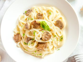 creamy mushroom pasta recipe in a bowl from above with parsley as garnish