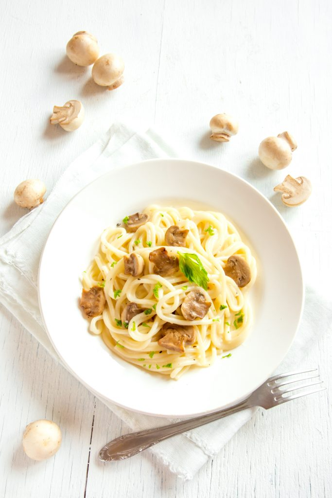 creamy mushroom pasta recipe on a table with a fork and uncooked mushrooms